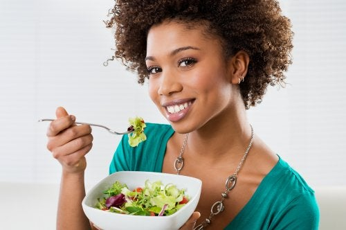 Mujer sonriente comiéndose una ensalada