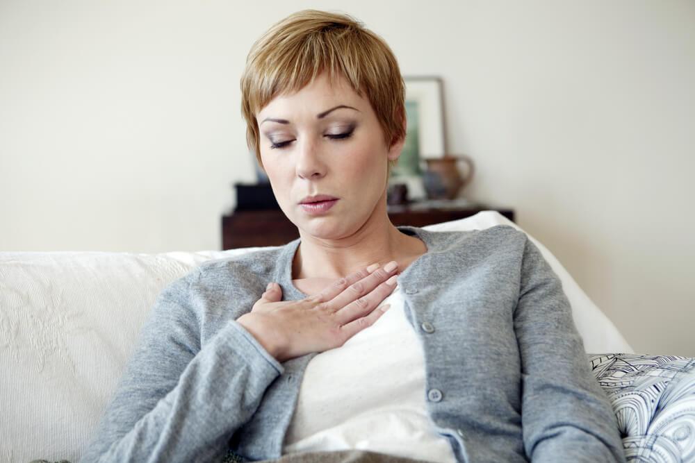 Mujer sufriendo un ataque de calor por estar en la edad de la menopausia