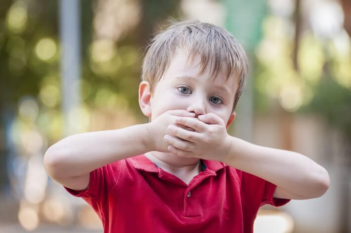 A child covering their mouth.