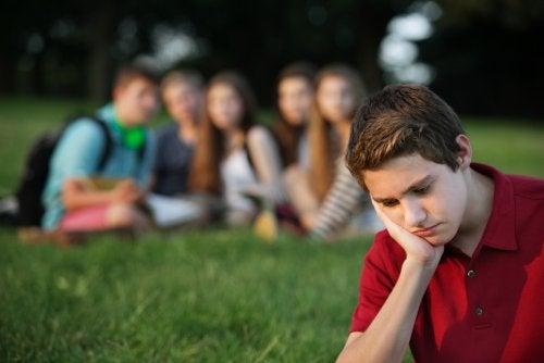 Grupo de adolescentes riéndose de un chico.