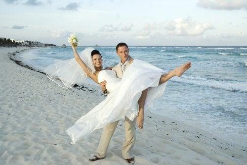 Novio sosteniendo a la novia en brazos en una playa