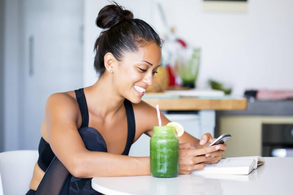 Deportista con el móvil bebiendo un zumo verde.