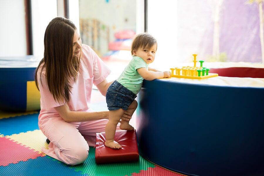 Bebé mantiene equilibrio con fisioterapeuta