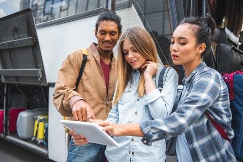 Grupo de amigos al lado de un autobus mirando una tablet.