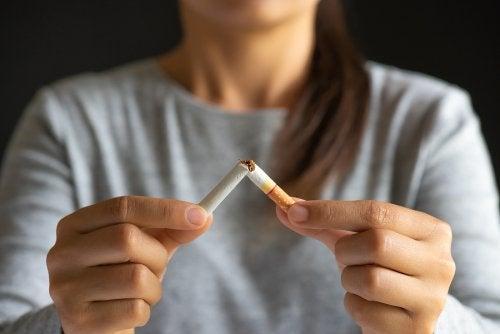 mujer rompiendo cigarrillo
