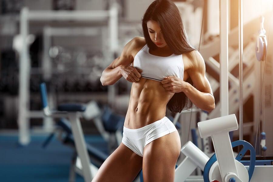 Mujer enseñando abdominales en el gimnasio.