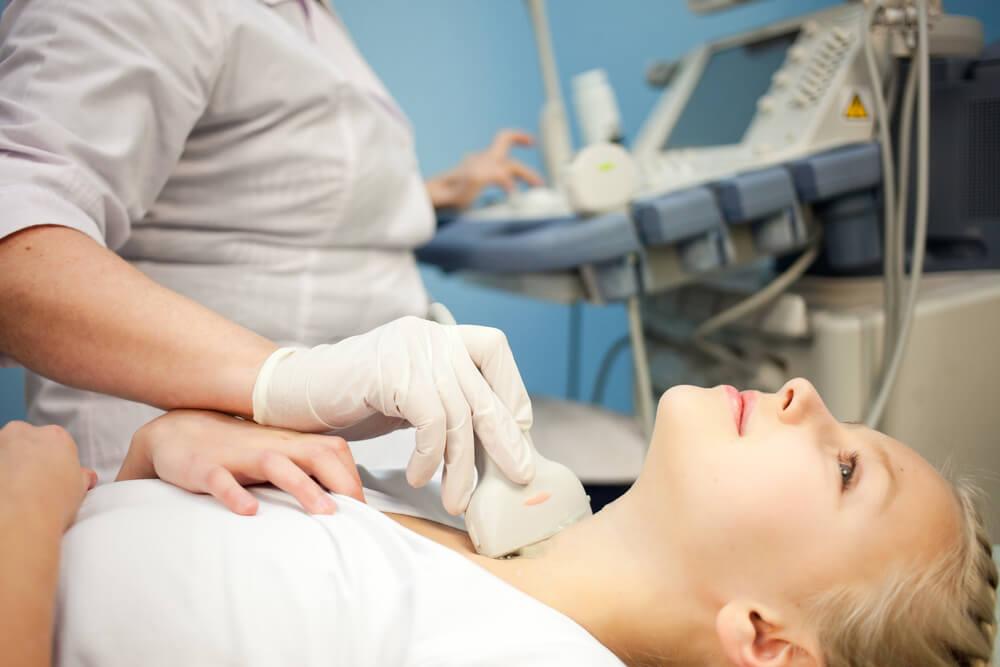 Mujer que se está sometiendo a una ecografía de tiroides.