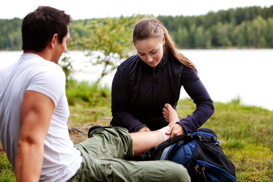 Mujer tratando un esguince de tobillo en el campo a un hombre.