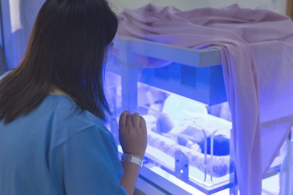Mujer al lado de una incubadora con un bebé.