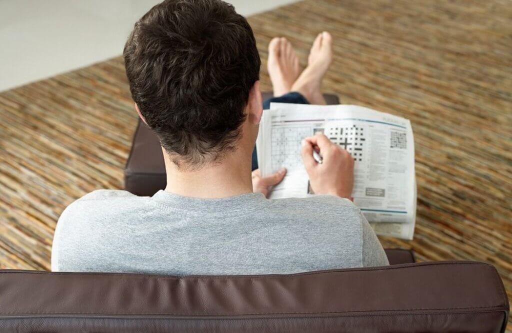 Hombre haciendo un crucigrama en el periódico.