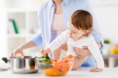 Mamá con bebé cocinando vegetales