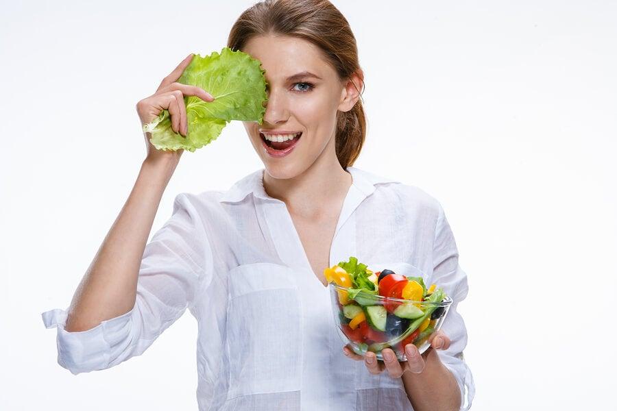 Mujer con bol de frutas y lechuga.