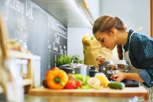 Mujer cocinando y oliendo la comida.