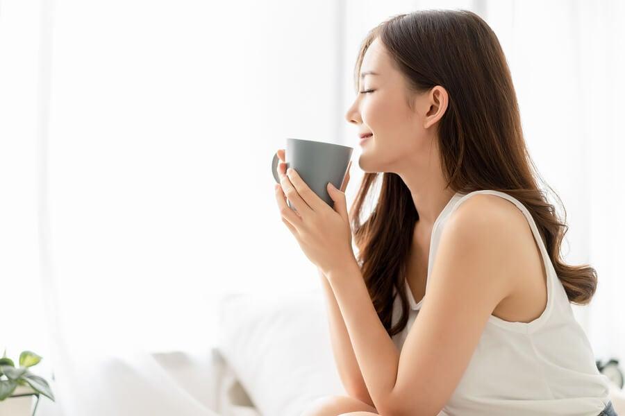 Mujer bebiendo té de pasiflora.