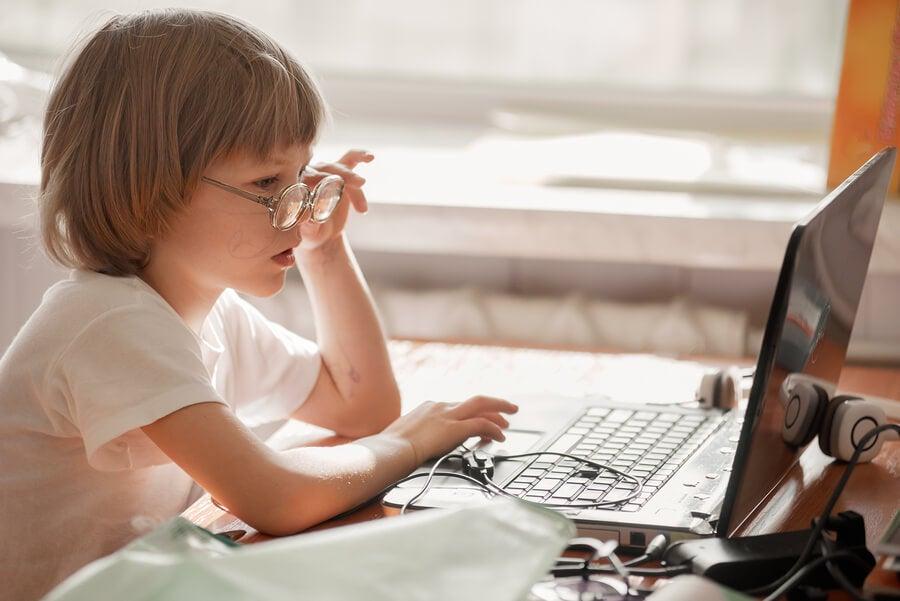 Niña con gafas usando ordenador