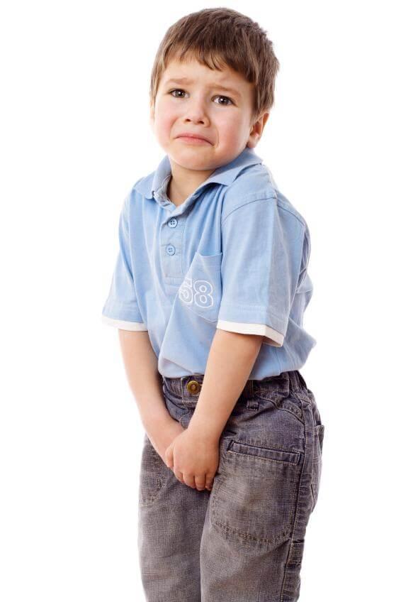 Niño preocupado con las manos en el pantalón.