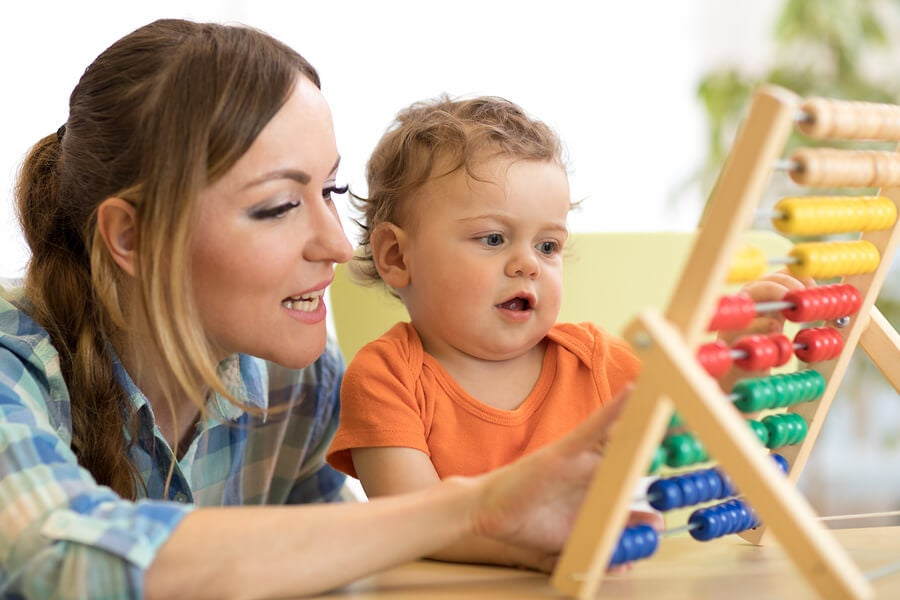 Niño y mamá con ábaco haciendo actividades para enseñar a su hijo a calcular.
