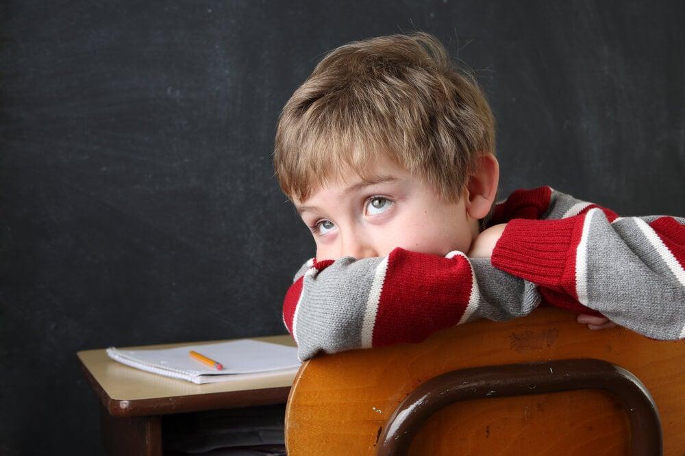 Niño sentado en un pupitre sin prestar atención a los deberes.