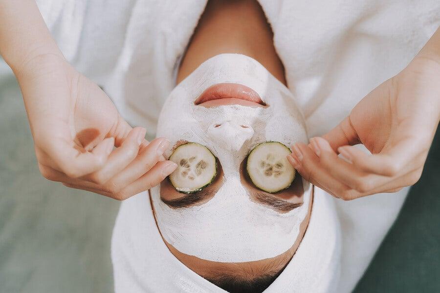 Mujer con mascarilla en la cara y pepino en los ojos.