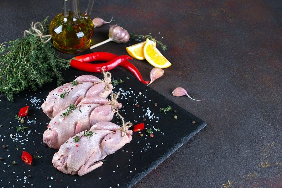 Plato con ingredientes crudos: perdiz o pollo, limones, pimientos y ajo.