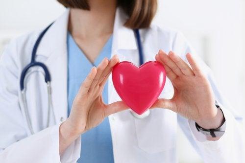 Médica con un corazón en las manos.