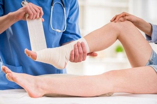 Médico vendando un tobillo