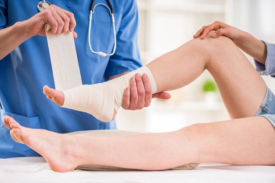 Médico vendando un tobillo.