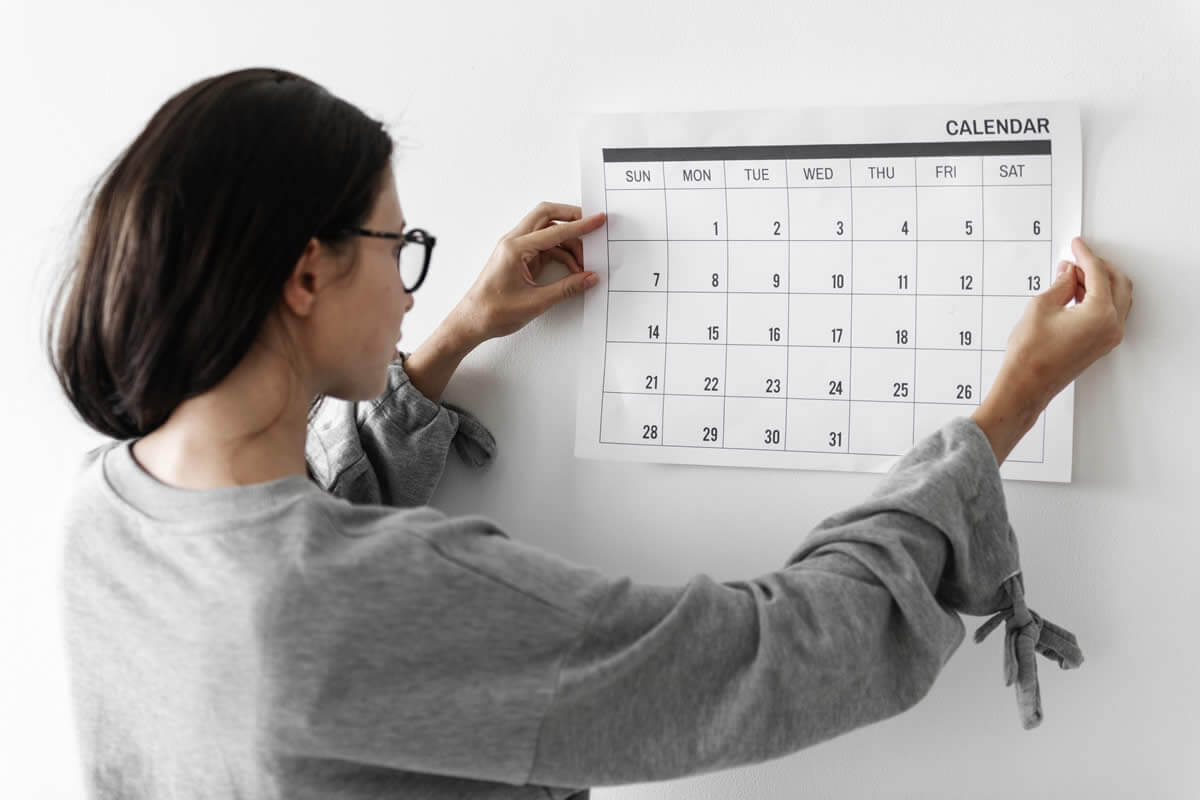 Mujer colgando un calendario en la pared.