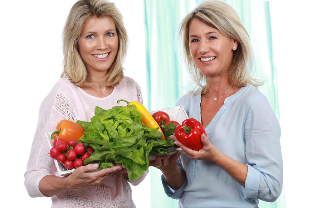 Dos mujeres con verduras en la mano.