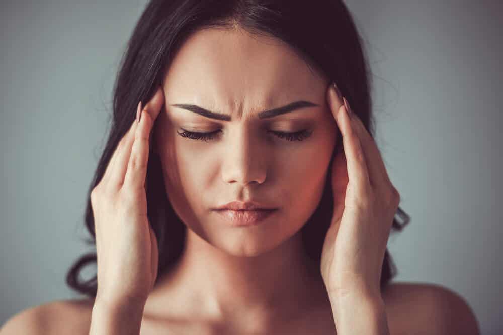 mujer apretándose las sienes debido a un fuerte dolor de cabeza