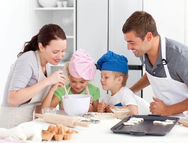 Familia con niños cocinando galletas.