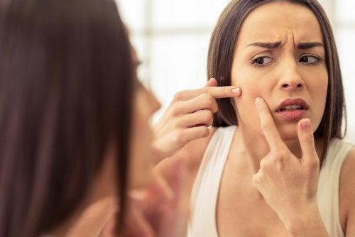 Mujer explotando espinillas en el rostro