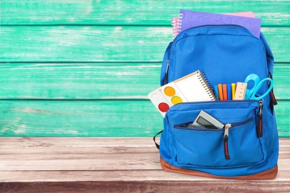 Mochila azul con cuadernos, rotuladores, tijeras y calculadora.