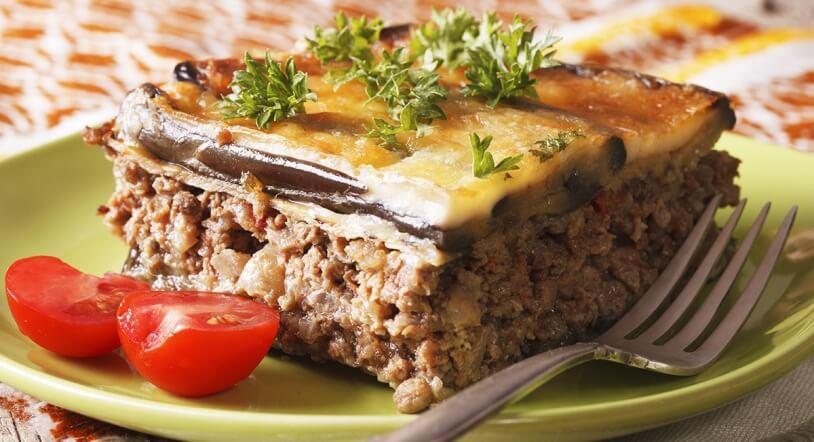 Porción de moussaka griega acompañada de tomates cherry y un tenedor.