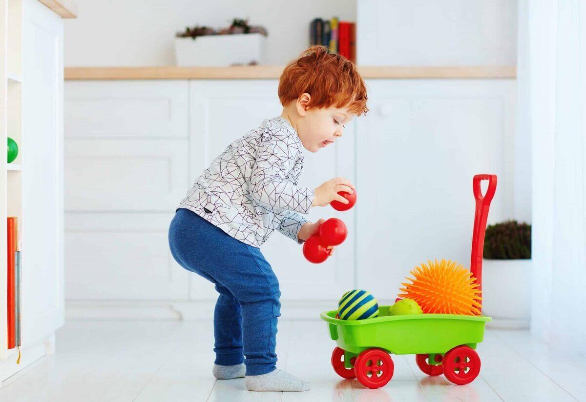 Niño ordenando sus juguetes.