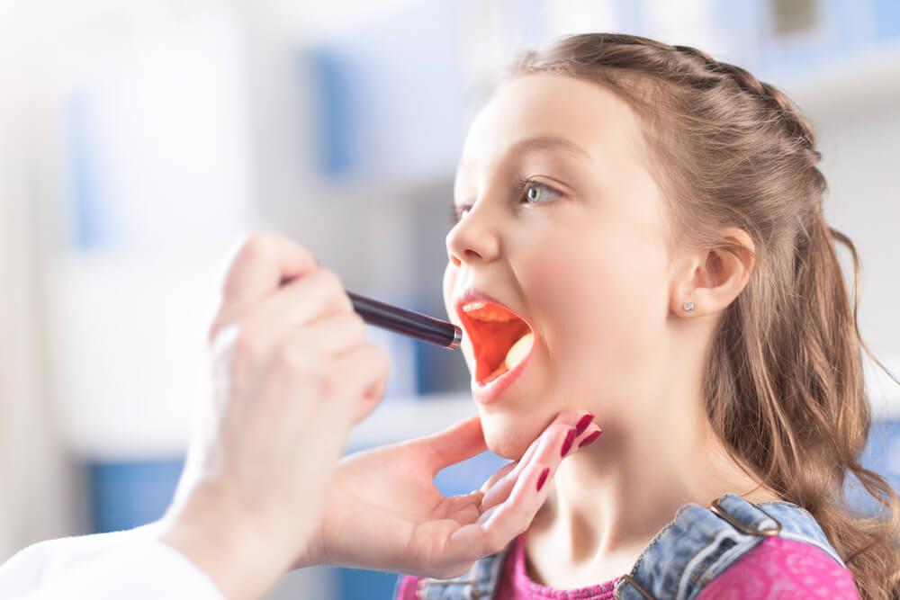 médico examinando la garganta de una niña