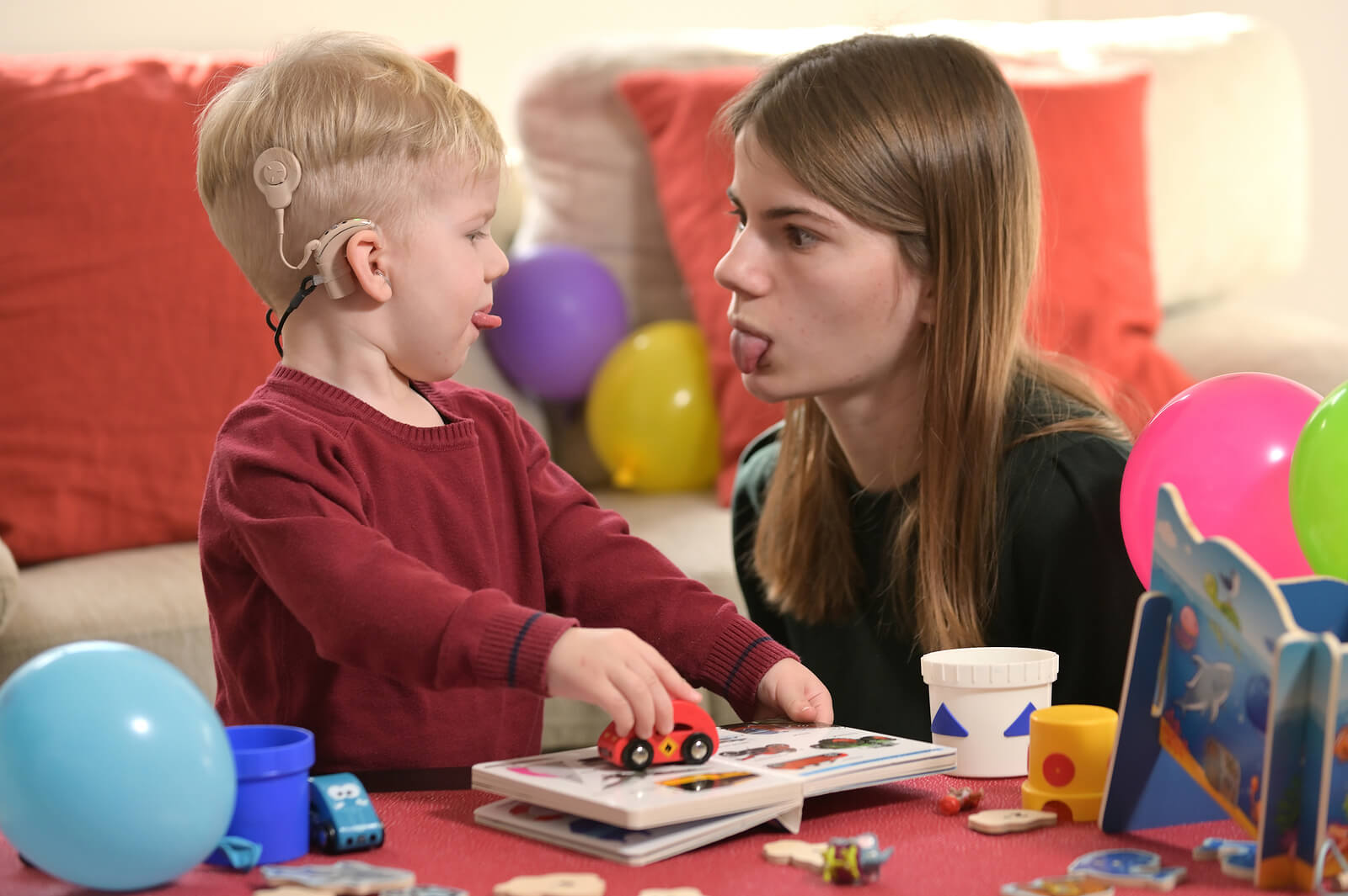 Niño con implantes cocleares jugando con su niñera.
