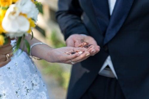 Pareja casándose con las arras en la mano