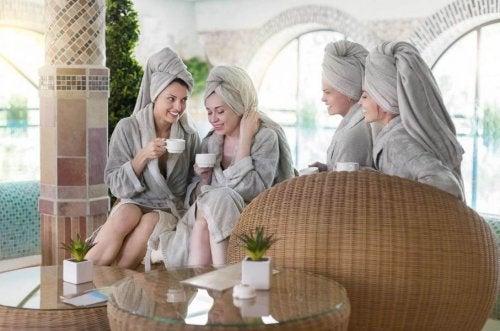 Mujeres en albornoz y toalla en la cabeza con tazas en la mano
