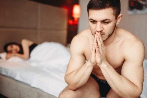 Hombre sentado en la cama mientras la mujer duerme
