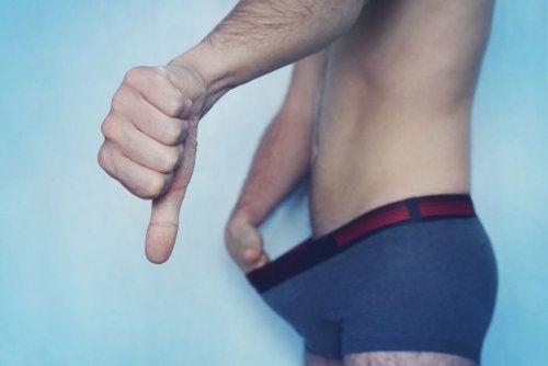 Hombre levantándose la ropa interior con el pulgar hacia abajo