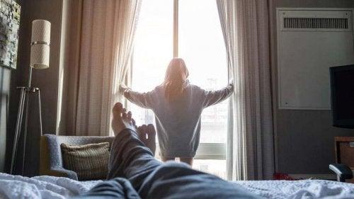 Mujer abriendo las ventanas y pareja tumbado en la cama