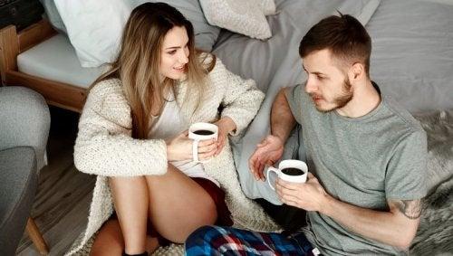 Pareja hablando a los pies de la cama con una taza de café
