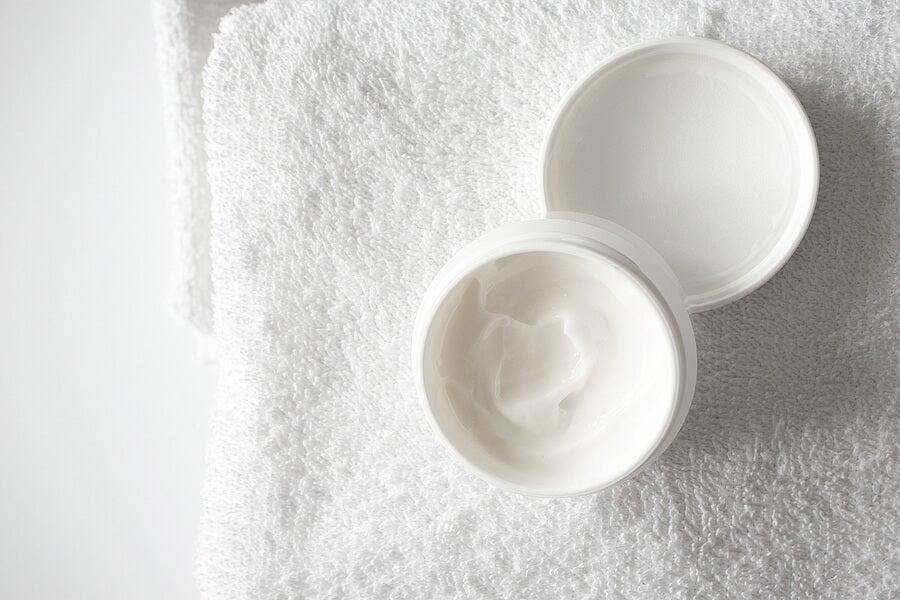 Bote de crema abierto sobre una toalla.