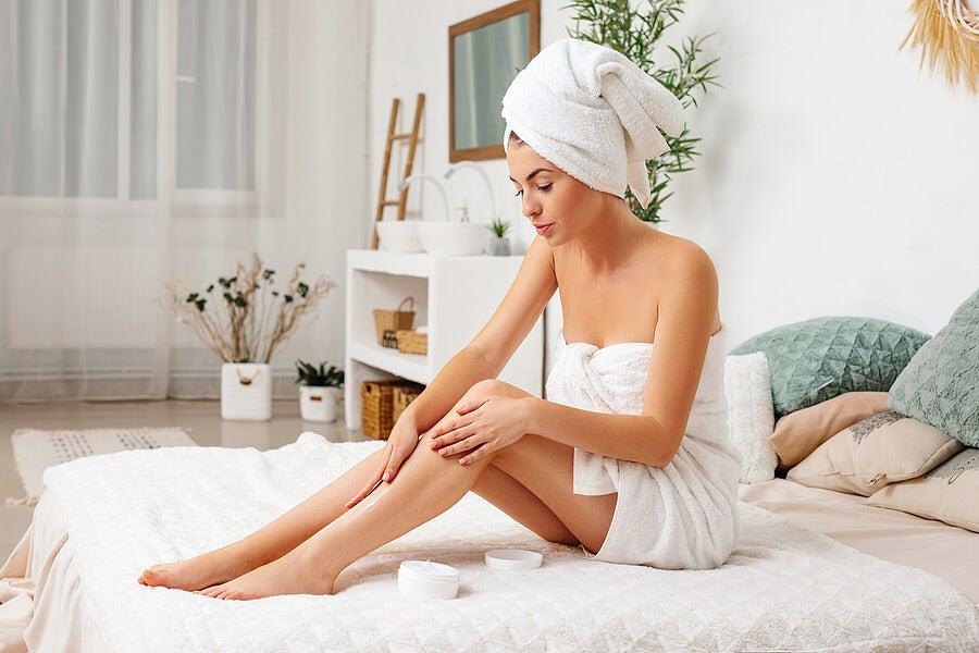 Mujer aplicándose crema en las piernas