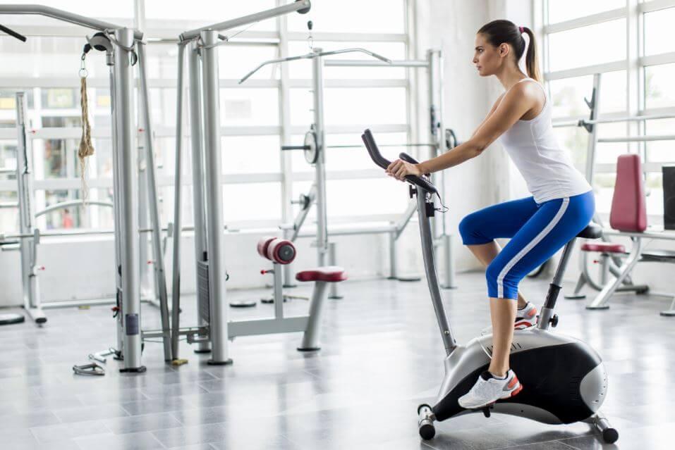 Mujer haciendo bicicleta estática en el gimnasio.
