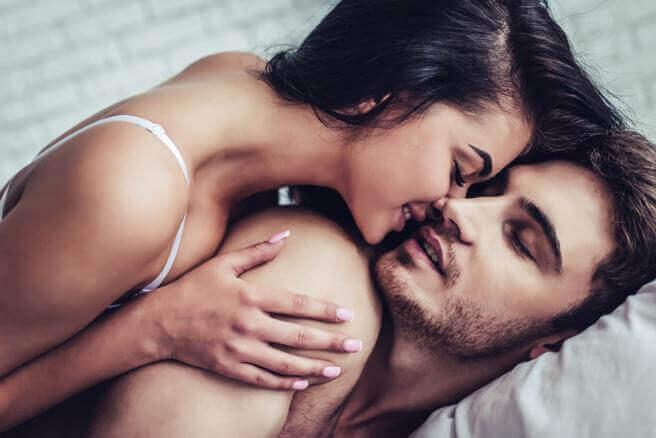 Pareja dándose un beso en la cama