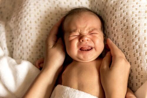Bebé llorando en la cama.