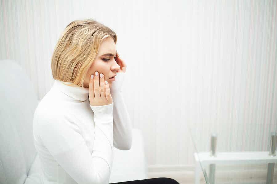 Mujer rubia que toca la mejilla porque tiene un dolor dental
