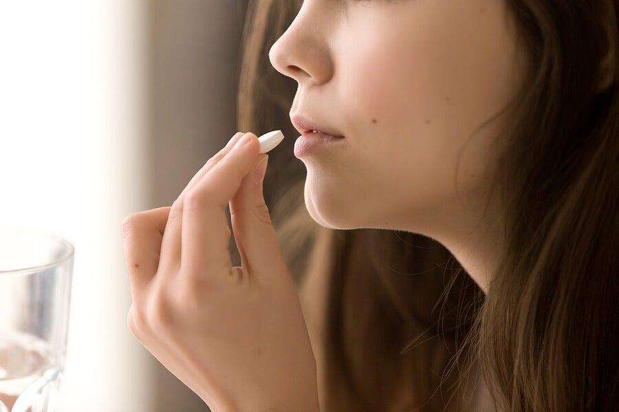 Mujer tomándose una pastilla
